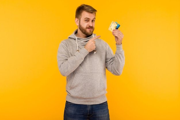 Привлекательный мужчина в серой толстовке с капюшоном указывает пальцем на кредитную карту, которую держит в руке на желтом фоне - изображение