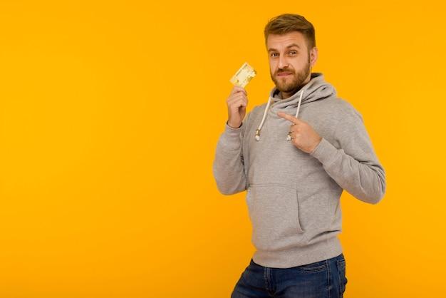 灰色のパーカーを着た魅力的な男性が、黄色の背景で手に持っているクレジットカードに指を向け