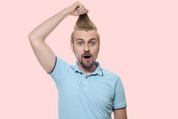 ターコイズブルーのtシャツを着た魅力的な男性が、驚いて口を開け、髪を上に引っ張って立っています。