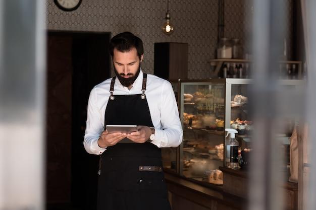エプロンバリスタまたは所有者の魅力的な男は、タブレットを保持しているコーヒーハウスに立っています
