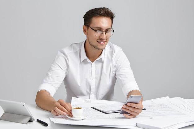 フォーマルな服装の魅力的な男性は、ハードワークの後に休憩し、コーヒーを飲み、スマートフォンでメッセージを入力し、嬉しい表情を見せています。白人のビジネスマンはコミュニケーションのために近代的な技術を使用しています