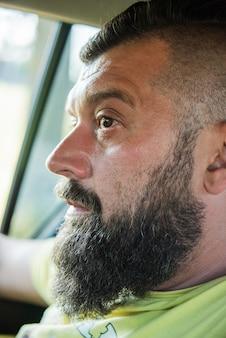 Привлекательный мужчина в хорошей машине. мужчина с бородой в машине. бородатый мужчина в машине не за рулем.