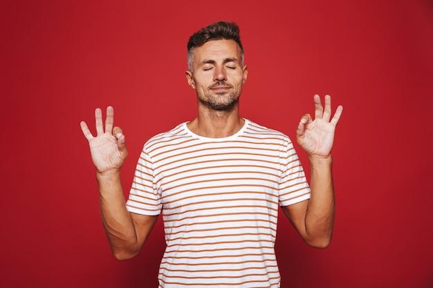 Привлекательный мужчина в полосатой футболке с закрытыми глазами, изолированными на красном, жестикулирует знаком ок