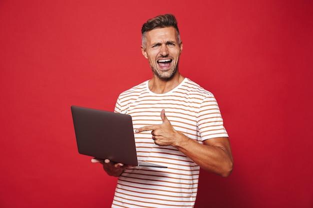 Привлекательный мужчина в полосатой футболке улыбается и держит серый ноутбук, изолированный на красном