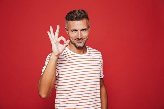Привлекательный мужчина в полосатой футболке улыбается и показывает знак ок, изолированные на красном