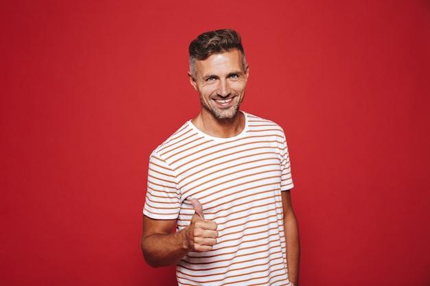 Привлекательный мужчина в полосатой футболке улыбается и показывает палец вверх изолирован на красном