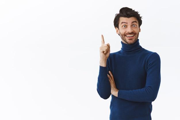 Привлекательный мужчина в стильном свитере с высоким воротом, поднял указательный палец в жесте эврики, радостно улыбаясь, нашел ответ, сделал интересное предложение, счастлив, наконец, решил проблему, белая стена