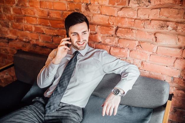 Привлекательный мужчина в костюме расслабленно сидит на диване и разговаривает по телефону