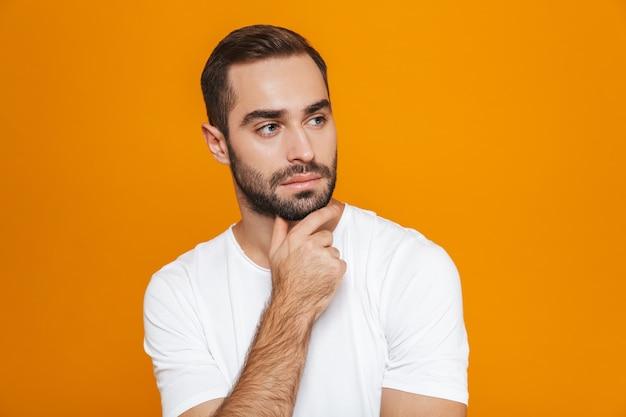 Привлекательный мужчина в футболке, касающийся подбородка стоя, изолированный на желтом