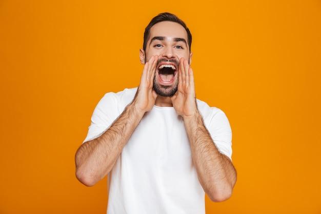 Привлекательный мужчина в футболке, когда звонит или кричит стоя, изолированный на желтом