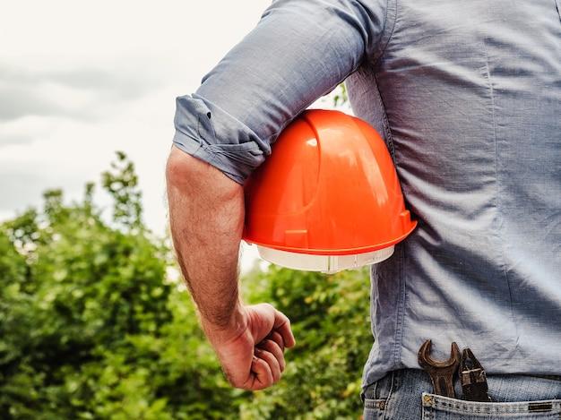 木々を背景に建設用ヘルメットを手に持って、作業服を着た魅力的な男