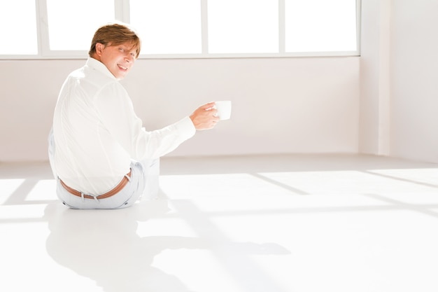 Attractive man and inviting someone to have a tea