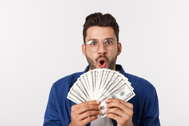 Attractive man is holding cash money in one hand, on isolated white