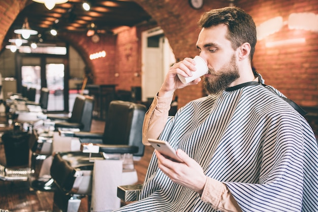 Attractive man is sitting in chair in barbershop and drinking some tea. also he is looking at the phone and reading something from it. he is waiting for a hairdresser.