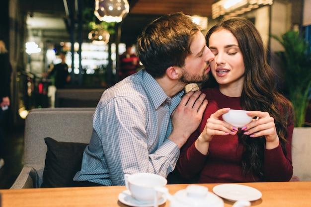 Привлекательный мужчина сидит со своей девушкой за столом и целует ее