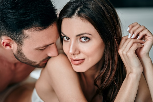 The attractive man kissing woman shoulder
