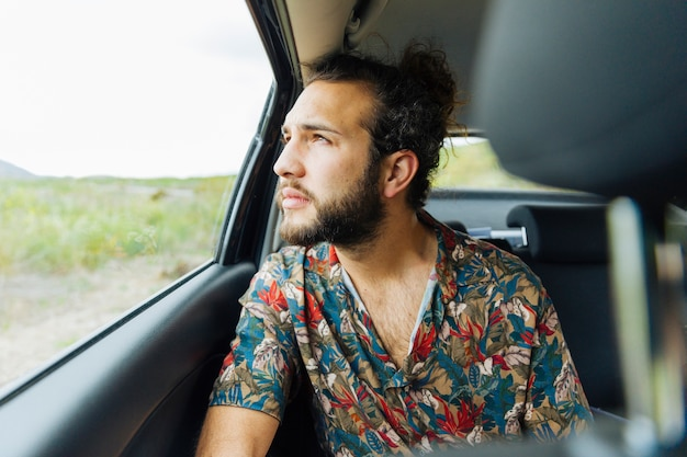 Attractive man looking up at car window