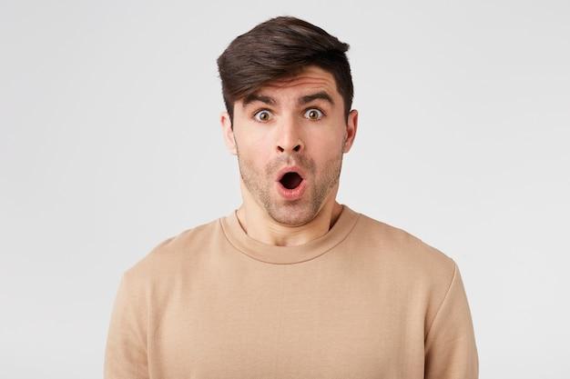 魅力的な男性は、正面を見て口を開けてショックを受けたように見えます肌色のセーターを着ています