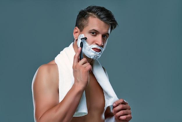 회색 배경의 매력적인 남자는 얼굴과 면도기에 면도 거품을 사용합니다. 남성 케어.
