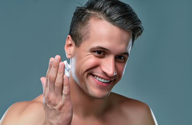회색 배경의 매력적인 남자는 얼굴에 면도 거품을 사용합니다. 남성 케어.
