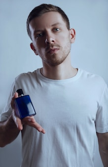 Attractive man and perfume on a blue