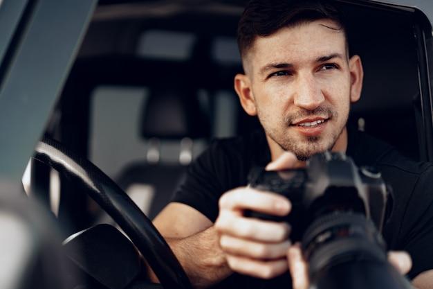 彼の車に座って写真を撮る魅力的な男性写真家