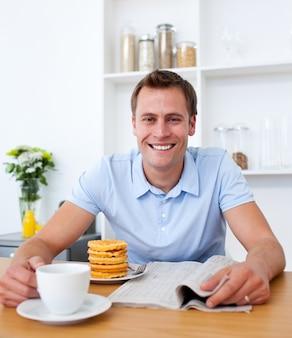 魅力的な男は、朝食を食べながら新聞を読む