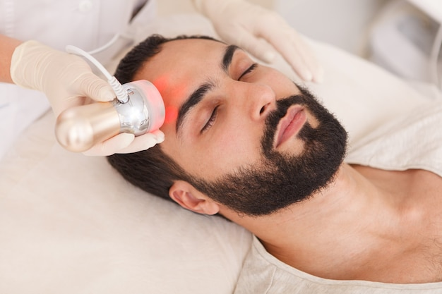 Attractive man relaxing while getting rf-lifting facial treatment at beauty clinic