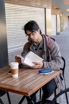 책을 읽는 동안 커피를 마시는 바에 앉아 매력적인 남자. 수직 방향