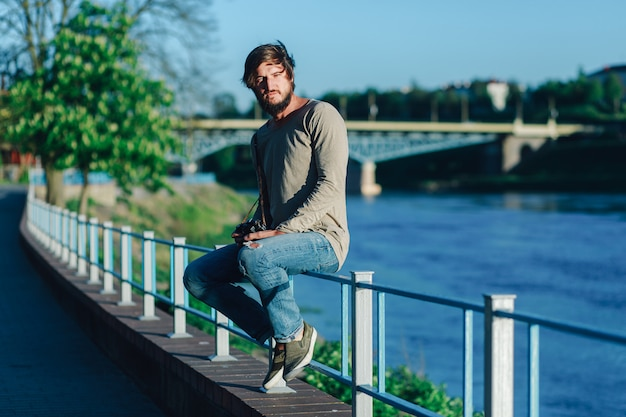 Attractive man sitting on railing on river bank and looking away