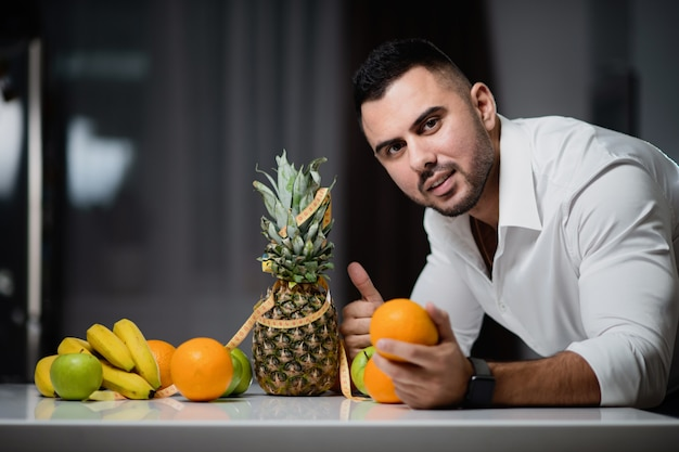 Attractive man sitting at a table on which lie fresh fruit