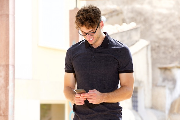 Attractive man smiling and holding mobile phone