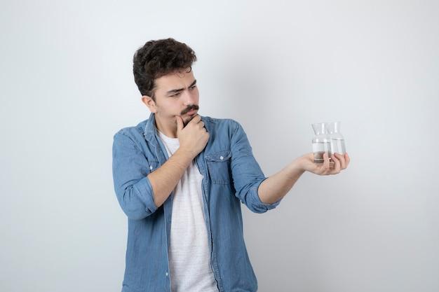 Un uomo attraente in piedi e con in mano barattoli di vetro