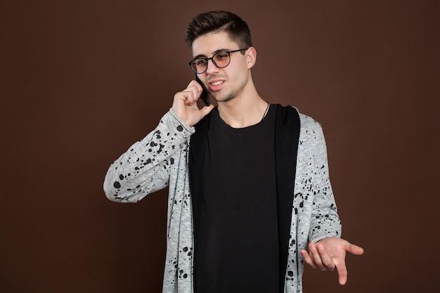 Привлекательный человек, стоящий на коричневом изолированном фоне и разговаривающий по мобильному телефону.