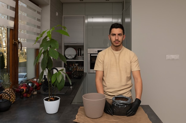 An attractive man transplanted an avocado seedling into a new, larger pot.