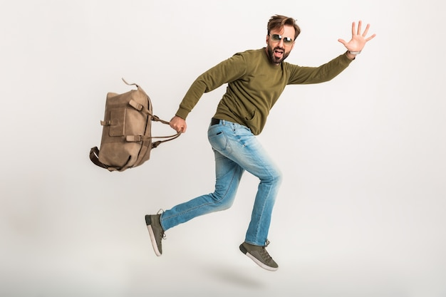 Attractive man traveler isolated running late with bag funny expression