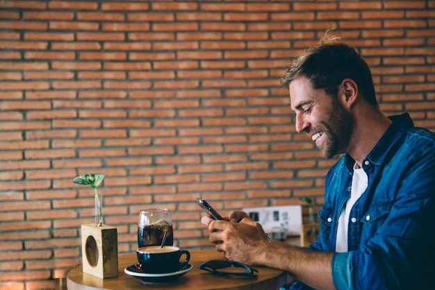 Attractive man using mobile phone having a coffee