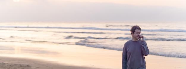 봄철 해질녘 해변을 걷고 있는 매력적인 남자가 스마트폰으로 이야기하고 있다