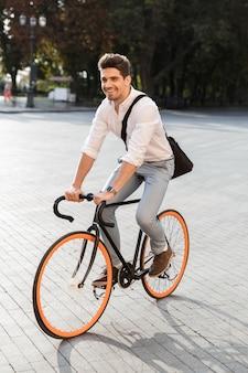 공식적인 옷을 입고 매력적인 남자, 도시 거리에서 자전거를 타고