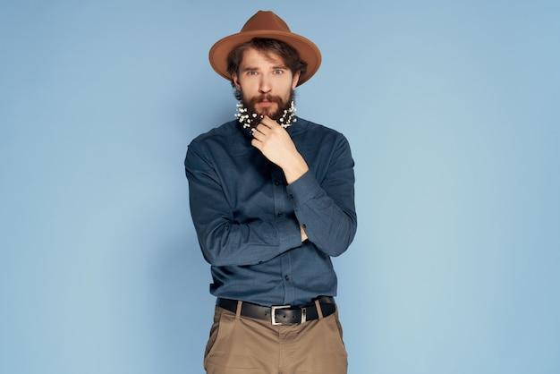 Привлекательный мужчина в шляпе с бородой с цветами украшения мода уход за волосами