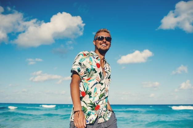 Привлекательный мужчина в гавайской рубашке на фоне моря или океана