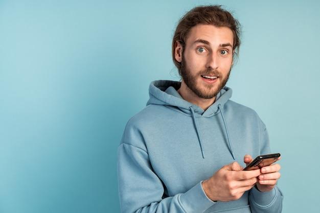 수염을 가진 매력적인 남자가 스마트 폰을 들고 있고, 그는 뭔가에 놀랐습니다.