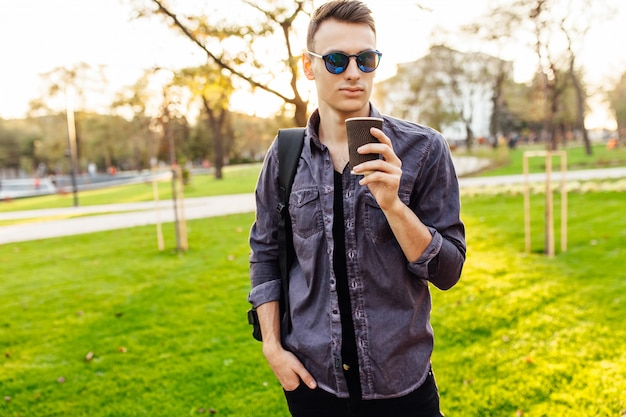 スタイリッシュな服、サングラスに身を包んだブリーフケースを持つ魅力的な男は、彼の手にガラスのコーヒーを保持し、公園を散歩します。