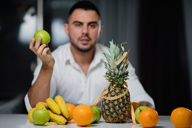 Attractive man with an apple in his hand sitting at a table on which lie fresh fruit