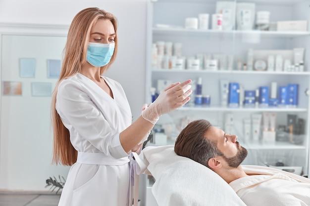 Привлекательный мужчина с бородой лежит на спине, перед массажем с подтяжкой лица. косметический массаж лица. концепция здоровья, красоты и релаксации.