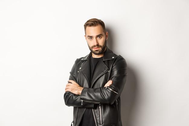 Привлекательный мужчина с бородой, одетый в кожаную куртку, улыбается, выглядит уверенно, скрестив руки на груди
