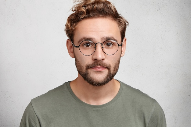 Attractive man with dark eyes, beard and trendy hairdo wears casual clothes and spectacles