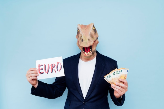 彼のお金とユーロを置くサインを保持している恐竜のマスクを持つ魅力的な男