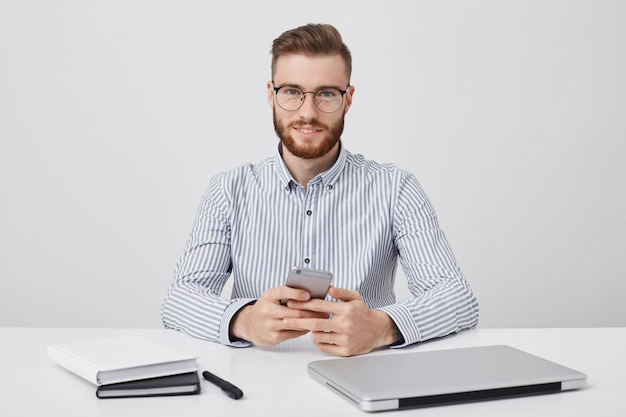 Attractive man with fashionable hairstyle and thick reddish beard, wears rounded glasses and formal shirt,