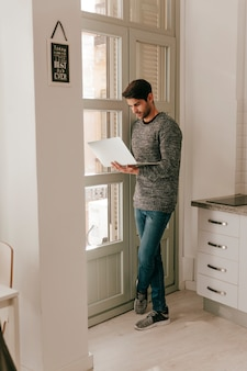 Attractive man with laptop near window